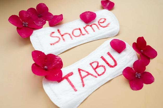 Assorbente da donna con scritta tabu e vergogna. concetto sociale astratto di vergognare le donne per il loro periodo mestruale