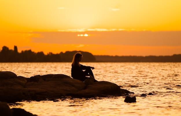 Siluetta della donna al tramonto che si siede sulla roccia che guarda diritto