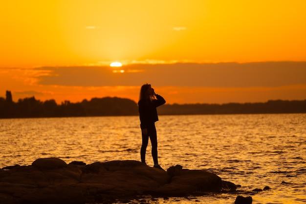 Silhouette di donna al tramonto in piedi sulla roccia guardando dritto