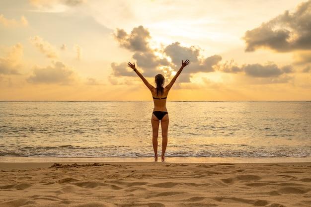 Silhouette di donna con le braccia alzate contro la tranquilla spiaggia al tramonto. libertà e sentirsi bene concetto
