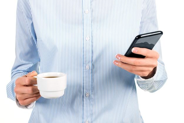 Tazza da tè e cellulare da donna. signora che tiene smartphone e tazza. leggere notizie fresche al lavoro. sono contento che sia completamente carico.