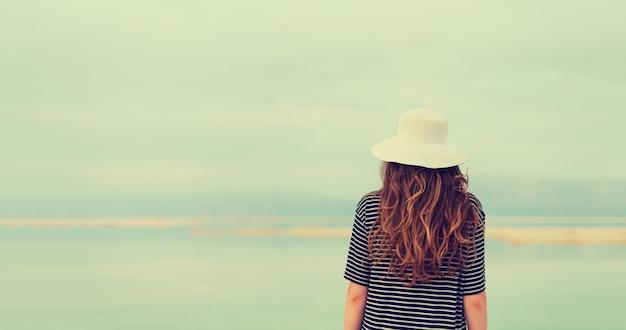 Donna in abito da marinaio a strisce vicino al mare della spiaggia del mar morto