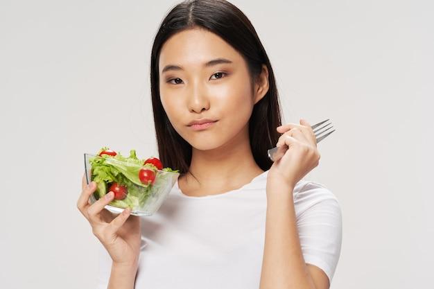 Piatti di insalate donna asiatico sembra tshirt sfondo chiaro