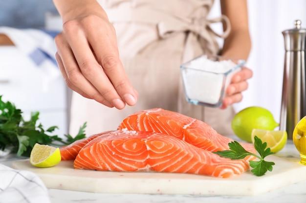 Donna salatura salmone crudo fresco a tavola, primo piano. delizia di pesce