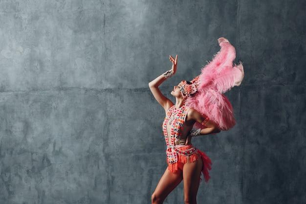 Donna in costume da samba o lambada con piumaggio di piume rosa.