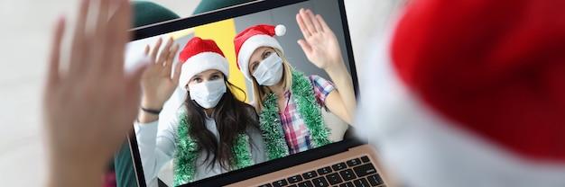La donna con il cappello di babbo natale tiene il laptop sulle ginocchia e comunica con i suoi amici in maschere protettive
