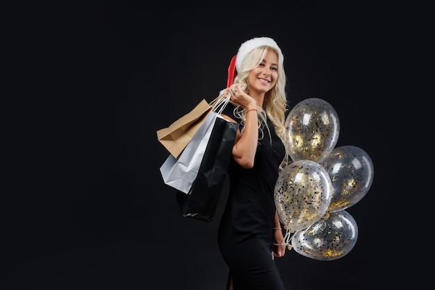 Donna in cappello della santa. festa di natale sul muro nero, borse della spesa e palloncini dorati