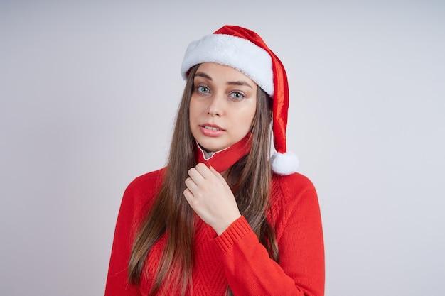 La donna in cappello della santa, maglione rosso, soffocamento rimuove una maschera protettiva