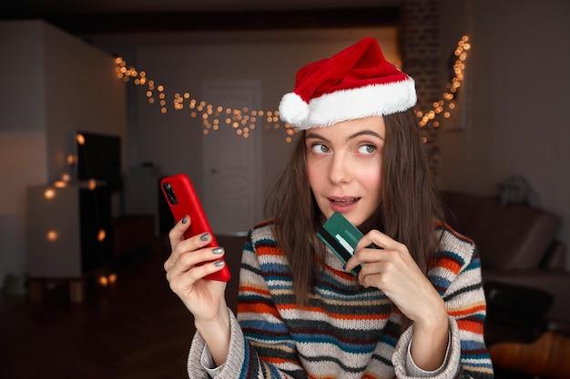 Donna in cappello della santa helper con smart phone e carta di credito che guarda lontano