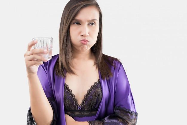 La donna in pigiama da notte e accappatoio viola che sciacqua e gorgoglia
