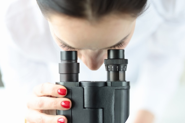 Chimico dello scienziato della donna che osserva tramite il primo piano del microscopio. concetto di diagnostica di laboratorio