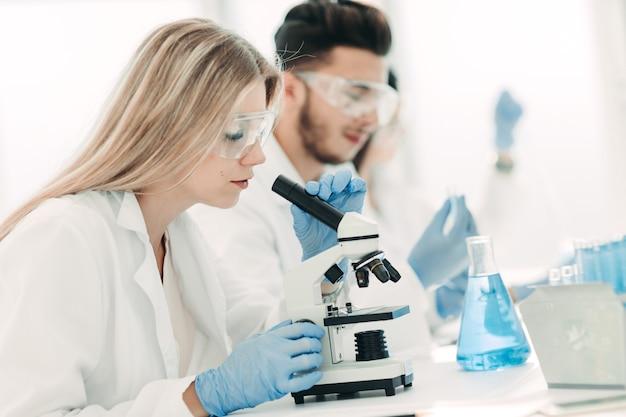 Scienziato della donna che conduce esperimenti con liquido