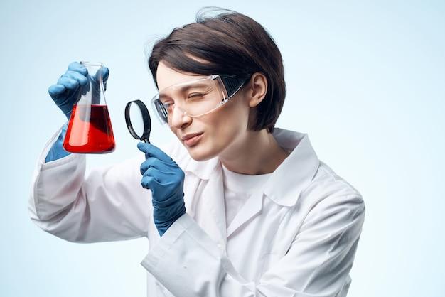 Scienziata che guarda attraverso una lente di ingrandimento una soluzione chimica lavora con la biotecnologia. foto di alta qualità