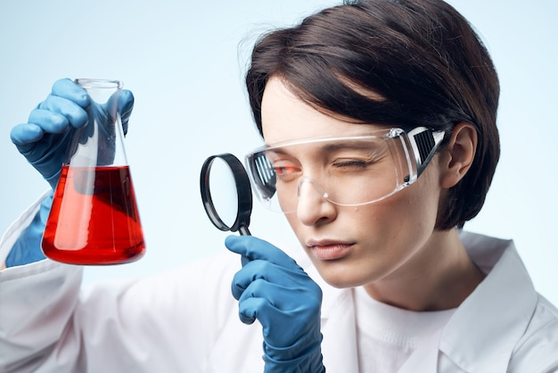 Scienziata che guarda attraverso una lente di ingrandimento una soluzione chimica lavora sulla biotecnologia