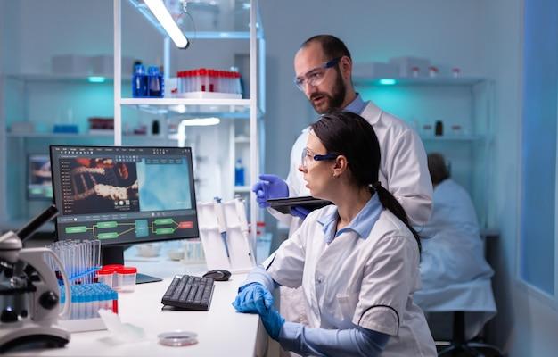 Scienziata e medico uomo che studiano le competenze sui virus nel laboratorio di medicina che lavorano con apparecchiature tecnologiche professionali