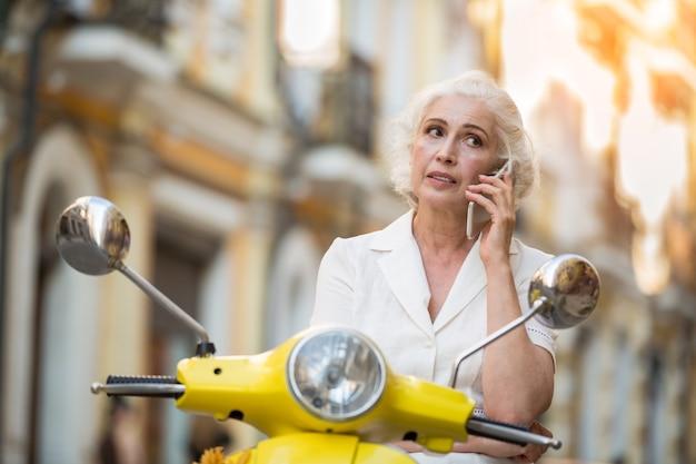Donna su scooter con telefono.