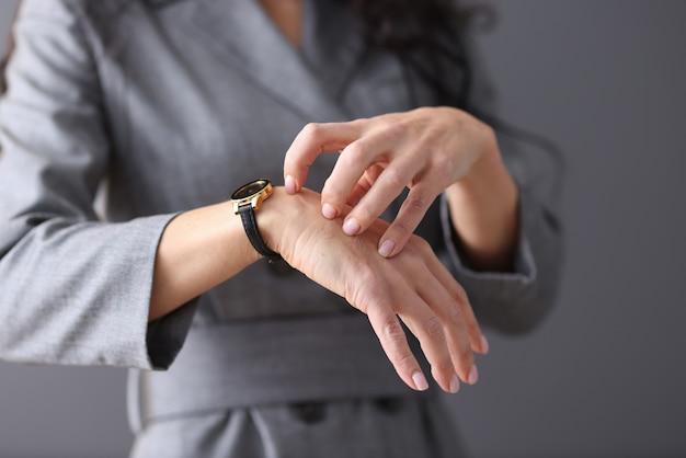 La donna si gratta la mano con le unghie. manifestazioni nevrotiche nel concetto di donne