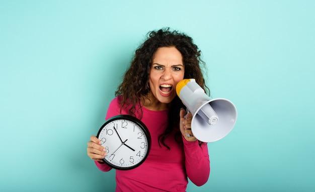 La donna urla con l'altoparlante perché è troppo tardi sfondo ciano espressione arrabbiata