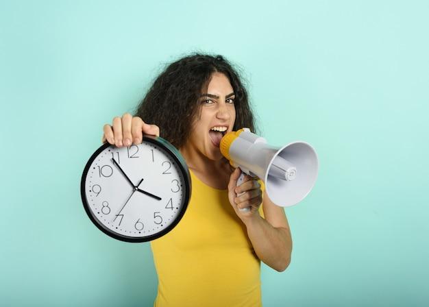 La donna urla con l'altoparlante perché è troppo tardi. espressione arrabbiata.