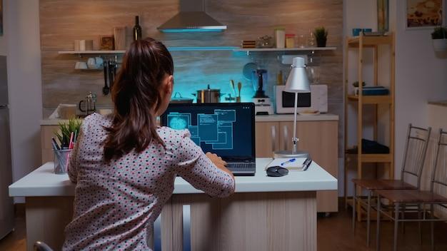 Donna che scorre i dati del codice di hacking di sicurezza di programmazione a tarda notte sul laptop. programmatore che scrive un malware pericoloso per attacchi informatici utilizzando il dispositivo ad alte prestazioni durante la mezzanotte.