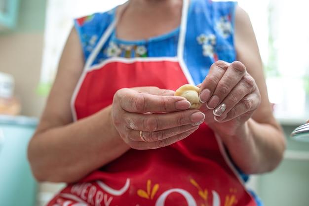 La donna scolpisce gnocchi in cucina, primo piano delle mani.