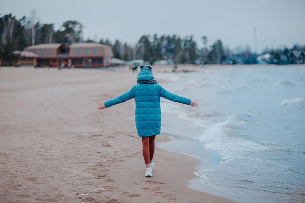 Donna sulla riva del mare in tempesta. costa del mare con acqua blu. onde sulla linea di costa, donna che cammina sulla spiaggia.