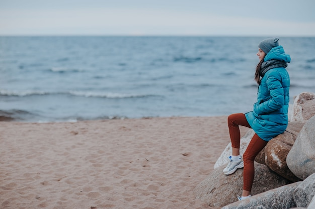 Donna sulla riva del mare in tempesta. donna sulle rocce sulla linea di costa.