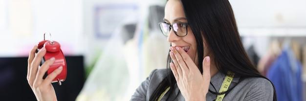 La sarta della donna guarda la sveglia rossa nelle scadenze del progetto a sorpresa durante il concept