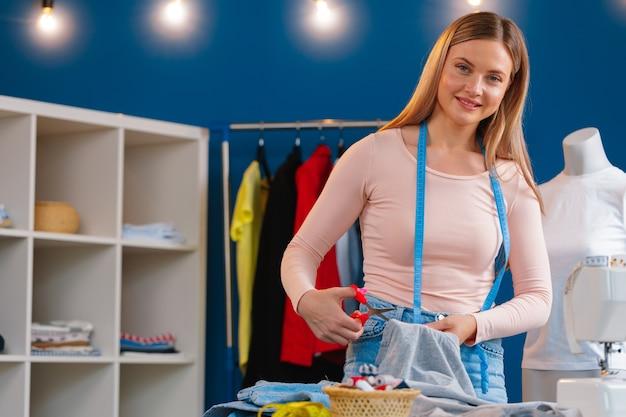 Sarta donna che lavora con il tessuto in fabbrica tessile