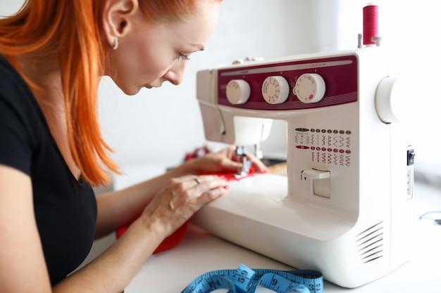 Sarta donna lavora su una macchina da cucire con un tavolo da lavoro di stoffa in un atelier di cucito