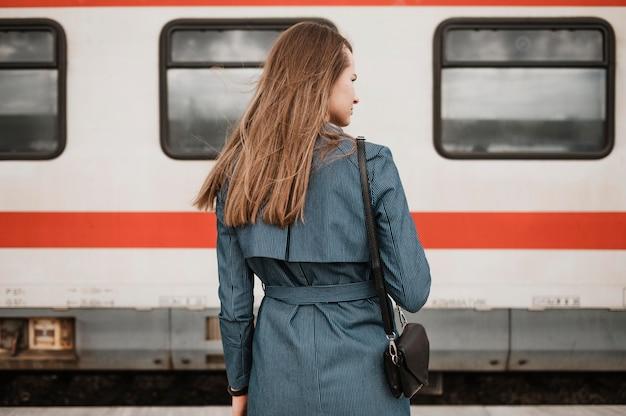 Donna che cerca il treno da dietro il colpo