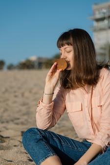 Donna seduta sulla spiaggia al tramonto e annusando pettine in legno fatto a mano. rilassante e concetto di cura.