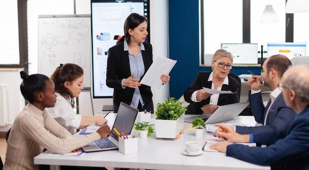Segretaria che porta documenti e caffè al direttore esecutivo mentre il team multietnico pianifica la strategia finanziaria durante la conferenza d'affari. manager briefing ai lavoratori del team durante il brainstorming.