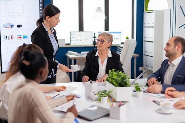 Segretaria che porta documenti e caffè al direttore esecutivo mentre il team multietnico pianifica la strategia finanziaria durante la conferenza d'affari