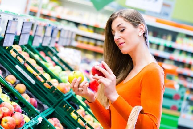 Donna che seleziona i frutti nel supemarket