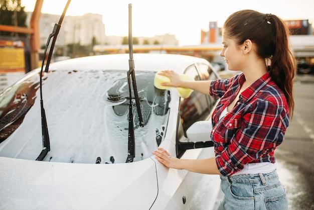 Donna in autolavaggio self-service, processo di autolavaggio. lavaggio del veicolo all'aperto in una giornata estiva. persona di sesso femminile con la spugna pulisce il vetro anteriore dell'automobile