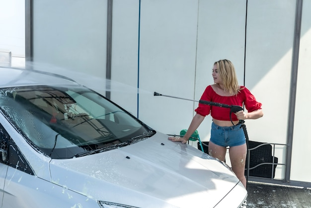 Donna alla stazione di autolavaggio self-service che lava via la schiuma dalla sua auto con un tubo ad alta pressione