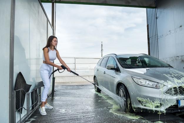 Donna alla stazione di autolavaggio self-service che lava via la schiuma dalla sua auto