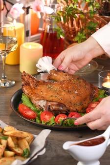 Donna che serve coscia di tacchino al forno su un vassoio di verdure sul tavolo da pranzo buon ringraziamento