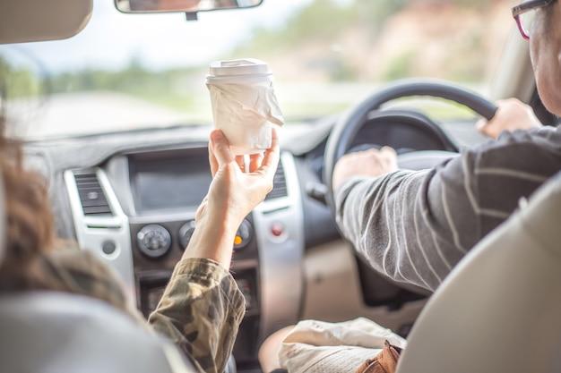Donna che serve la tazza di caffè caldo al suo fidanzato in macchina