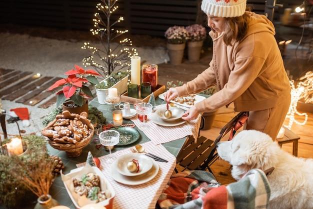 Donna che serve e decora un tavolo da pranzo festivo alla vigilia di natale all'aperto sulla terrazza