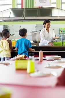 Donna che serve cibo agli scolari