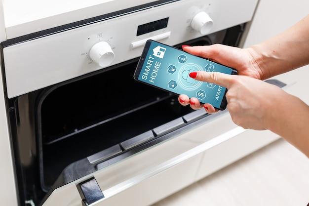 La donna imposta il programma di cottura al forno. concezione dell'utilizzo dell'applicazione casa intelligente.