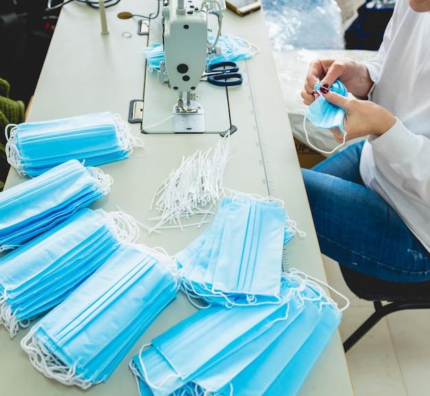 La donna cuce il medico facciale alla macchina per cucire. pandemia da coronavirus.