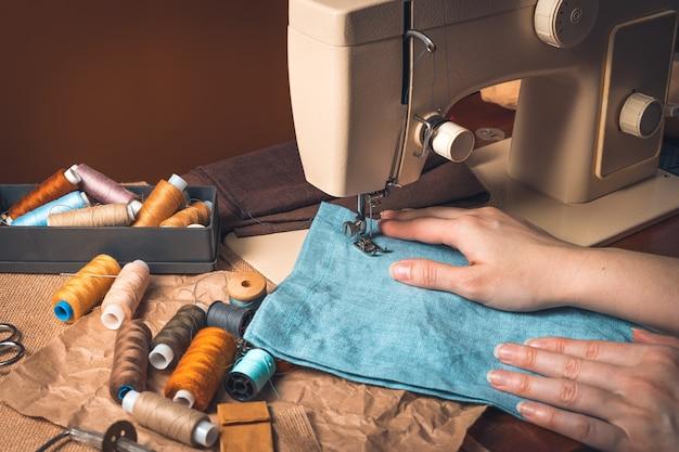 Una donna cuce su una macchina da cucire su uno sfondo marrone. il concetto di cucito.