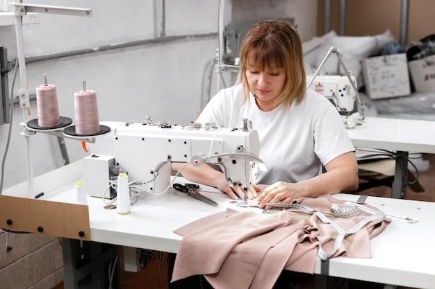 La donna cuce sulla macchina da cucire in fabbrica