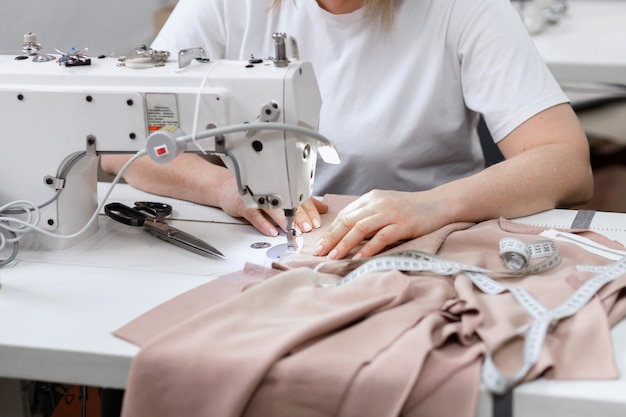La donna cuce dietro la macchina da cucire al lavoro