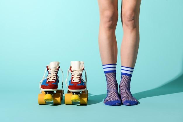Donna in calze a rete blu sexy con un paio di pattini a rotelle colorati