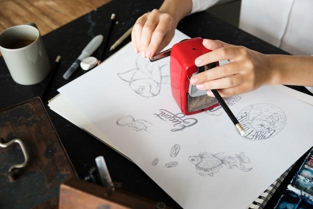 La donna affila la matita su una tavola nera