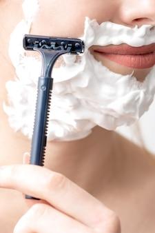 Donna che rade il suo fronte dal rasoio